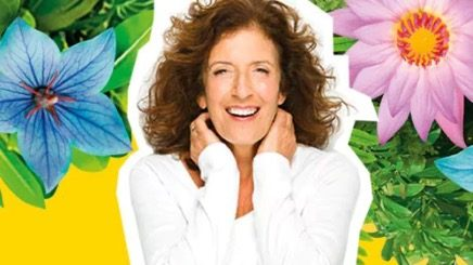 Anita Roddick pictured against large tropical flowers